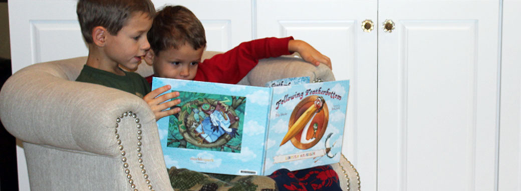 Two little boys reading Finding Featherbottom in a chair