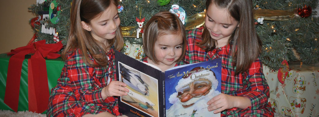 Three little girls reading under a Christmas tree